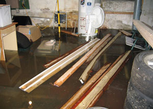 A severely flooding basement in Clinton, with lumber and personal items floating in a foot of water